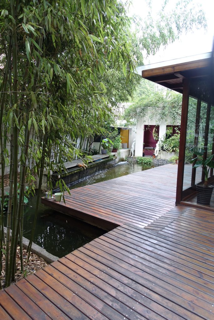 Picture of exterior of hostel with a koi pond and plants